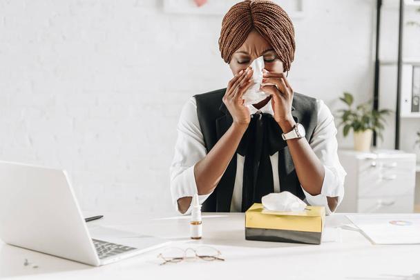 beteg afrikai-amerikai felnőtt üzletasszony szenved, hideg, és segítségével szövetek íróasztal hivatalban - Fotó, kép