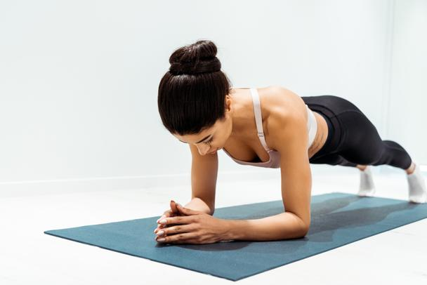 Young wonderful sportive girl doing plank exercise in sports centre - Photo, Image