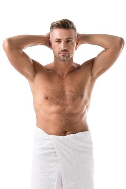 adult muscular shirtless man wrapped in towel posing with raised arms isolated on white - Photo, Image