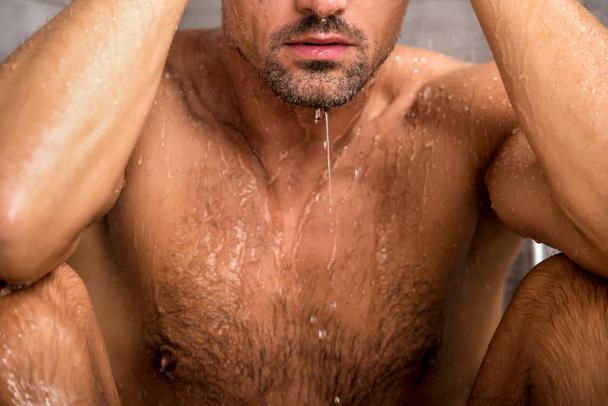 cropped image of man sitting under shower during morning time - Photo, Image