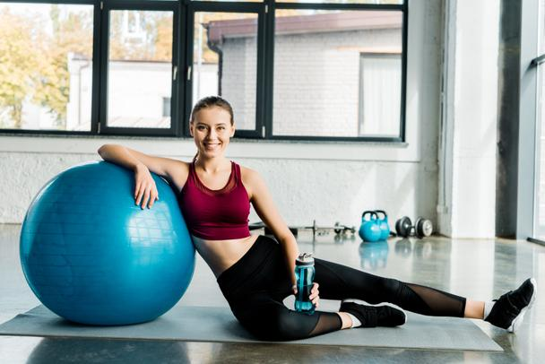 beautiful fit sportswoman looking at camera and sitting on mat with blue fitness ball at sports center - Photo, Image