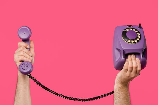 cropped shot of man holding purple rotary phone isolated on pink - Photo, Image
