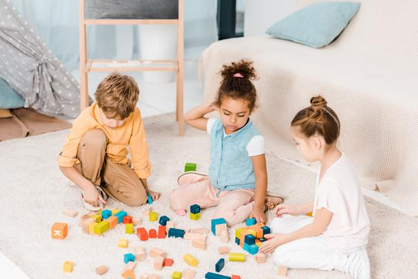 high angle view of adorable multiethnic children playing with colorful cubes on carpet   - Photo, Image