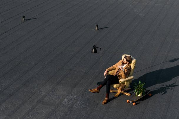 adult businessman resting in armchair with cigarette on roof  - Photo, Image