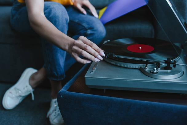cropped image of mixed race girl turning on gramophone with retro vinyl at home - Photo, Image