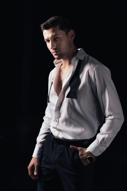 handsome man in white shirt and hand in pocket looking at camera while posing isolated on black - Photo, Image