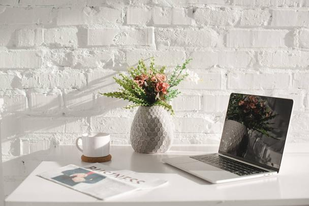 laptop with blank screen in white kitchen near business newspaper - Photo, Image