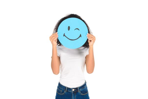 african american girl holding round, blue sign with winking face expression isolated on white - Photo, Image