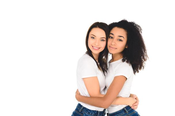 multicultural friends in white T-shirts hugging and looking at camera isolated on white - Photo, Image