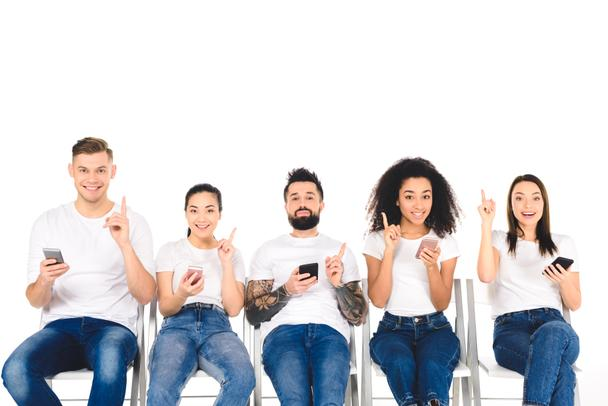 multicultural group of young people using smartphones and showing idea signs isolated on white - Photo, Image