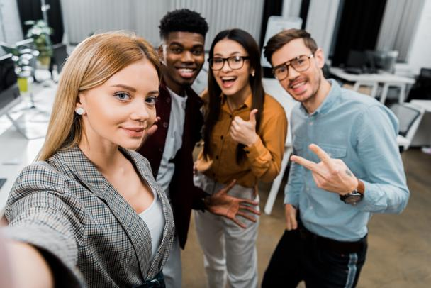 camera point of view of smiling multicultural colleagues taking selfie together in office - Photo, Image