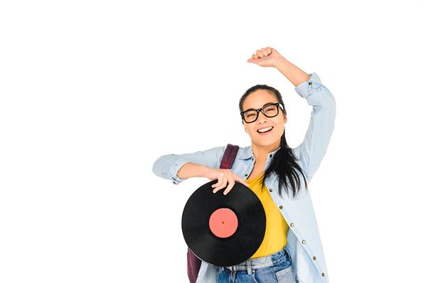 happy girl in glasses holding vinyl record with hand above head isolated on white - Photo, Image