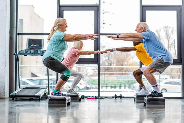 side view of mature athletes synchronous doing squats on step platforms at gym - Photo, Image