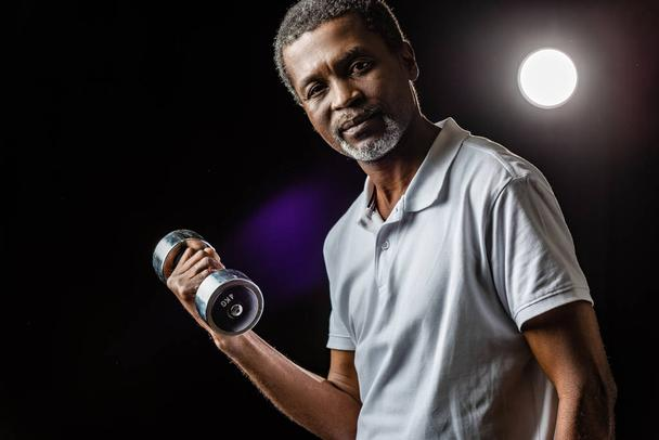 middle aged african american sportsman exercising with dumbbell on black with spotlight - Photo, Image