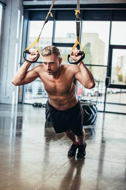 handsome shirtless sportsman exercising with resistance bands in gym  - Photo, Image