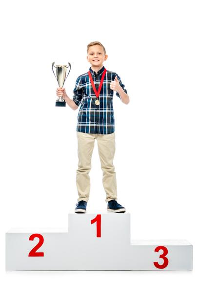 smiling boy standing on winner pedestal, holding trophy cup, showing thumb up and looking at camera isolated on white - Photo, Image