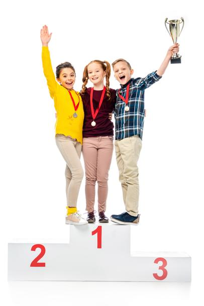 happy kids with medals and trophy cup standing on winner pedestal, shouting and looking at camera isolated on white - Photo, Image
