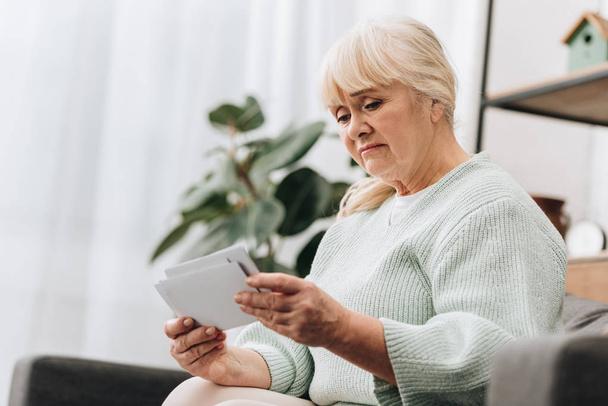 Traurige Seniorin mit blonden Haaren schaut sich Fotos an  - Foto, Bild