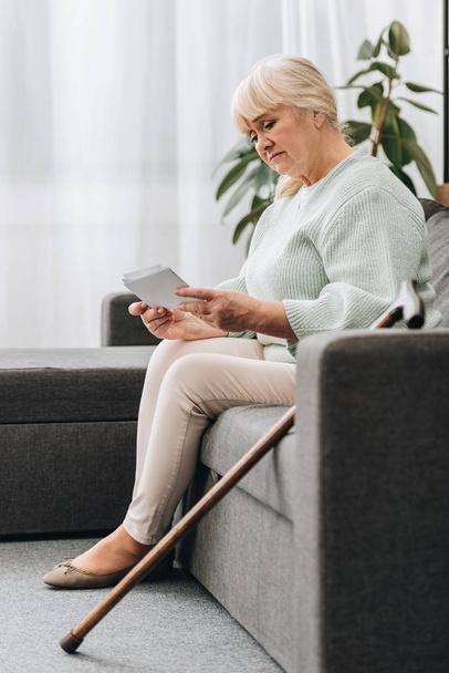 Traurige Rentnerin mit blonden Haaren schaut sich Fotos an, während sie auf dem Sofa sitzt - Foto, Bild
