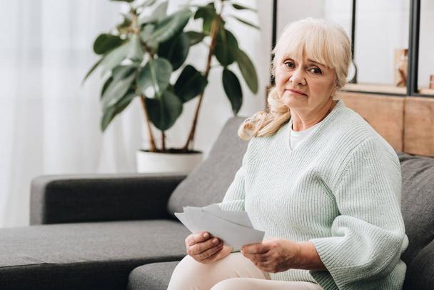 Traurige Rentnerin mit blonden Haaren hält Fotos hoch - Foto, Bild