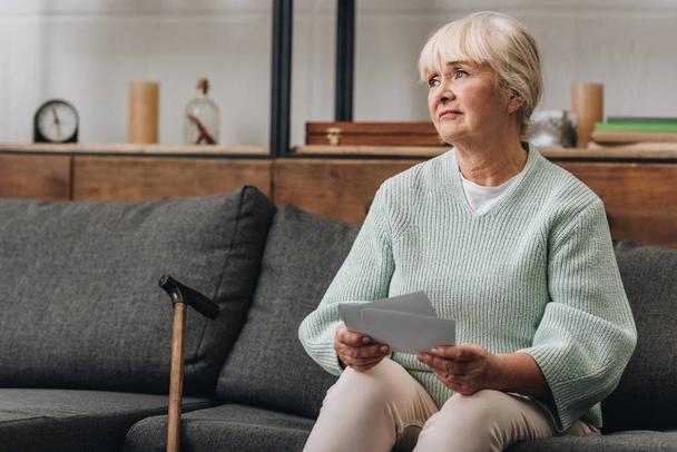 Verärgerte Rentnerin mit blonden Haaren hält alte Fotos hoch, während sie auf Sofa sitzt - Foto, Bild