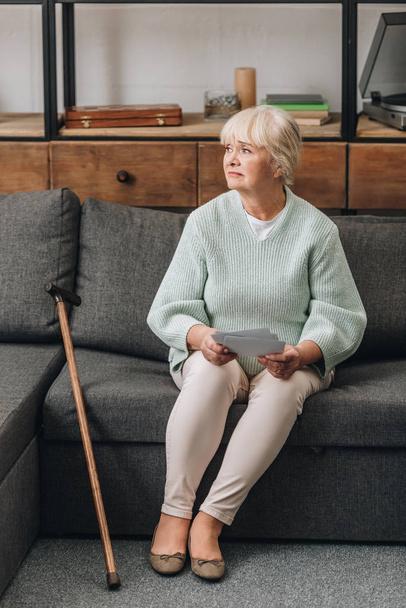 Verärgerte Rentnerin mit blonden Haaren hält Fotos hoch, während sie im Wohnzimmer auf dem Sofa sitzt  - Foto, Bild