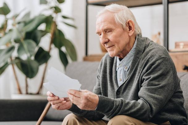 Glückliche Rentnerin mit grauen Haaren schaut sich Fotos im Wohnzimmer an - Foto, Bild