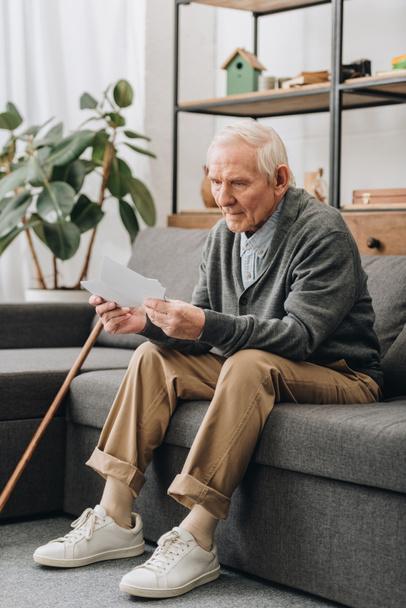 Trauriger Rentner mit grauen Haaren schaut sich Fotos an, während er auf dem Sofa sitzt  - Foto, Bild