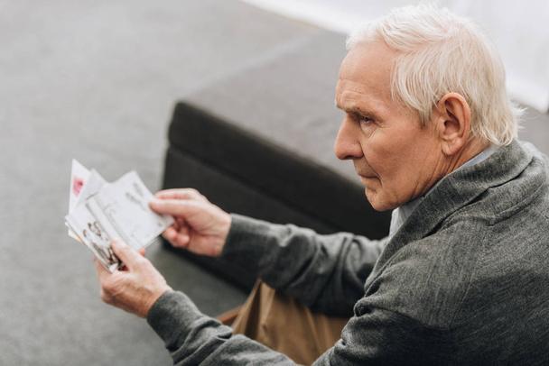 Trauriger Rentner mit grauen Haaren schaut sich zu Hause alte Fotos an - Foto, Bild