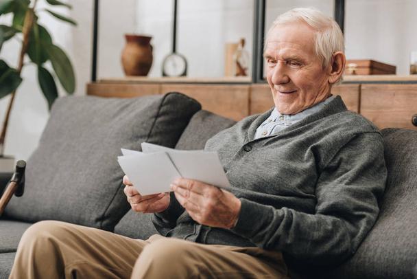 glücklicher älterer Mann mit grauen Haaren schaut sich Fotos an und sitzt auf dem Sofa - Foto, Bild
