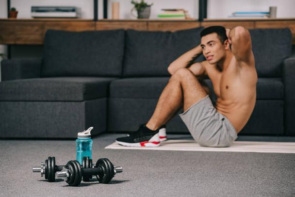 selective focus of dumbbells near sport bottle with bi-racial man on background  - Photo, Image