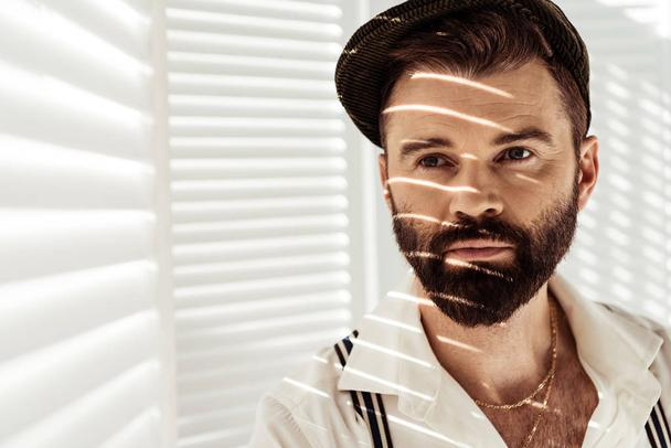 handsome bearded man in cap near white room divider - Photo, Image