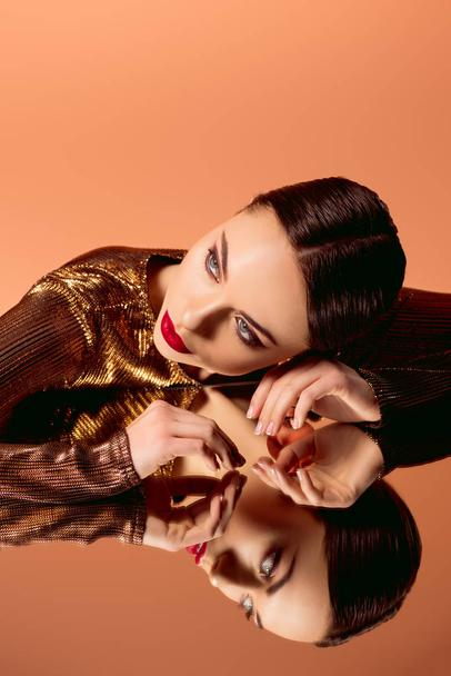 beautiful woman in golden clothes with glamorous makeup and mirror reflection posing isolated on orange - Photo, Image
