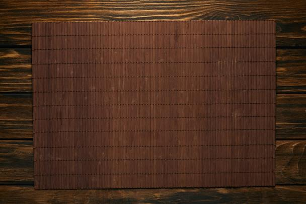 top view of empty brown bamboo mat on wooden table - Photo, Image