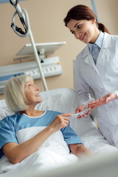 усміхнене жіночий лікар давати таблетки для старших жінка, лежачи на лікарняному ліжку - Фото, зображення