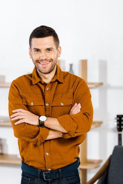 cheerful man standing with crossed arms in living room  - Photo, Image