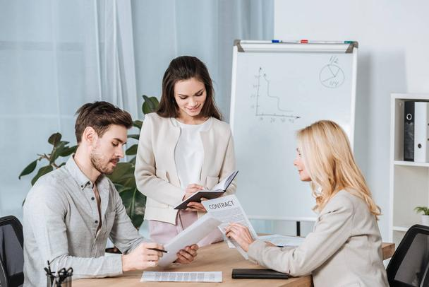smiling young businesswoman writing in notebook and colleagues working with papers in office - Photo, Image