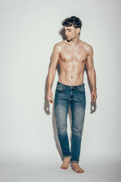 sexy shirtless muscular macho in jeans posing on grey - Photo, Image