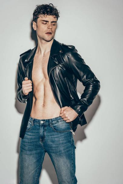 handsome sexy rocker posing in jeans and black leather jacket on grey - Photo, Image