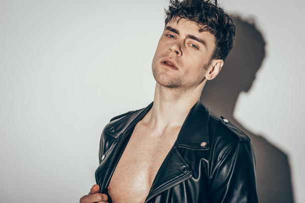 handsome sexy shirtless man posing in black leather jacket on grey - Photo, Image