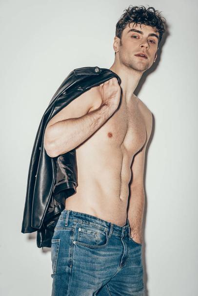 sexy shirtless man posing with black leather jacket on grey - Photo, Image