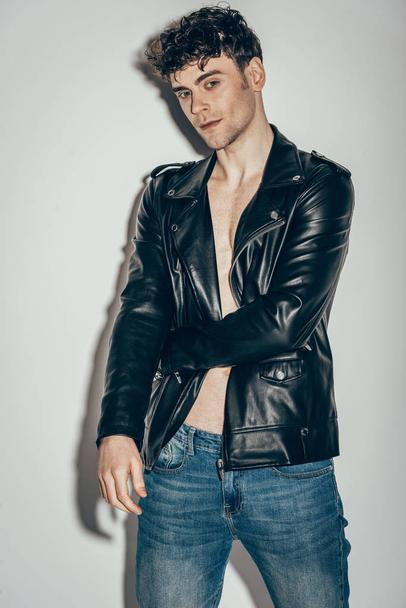 stylish sexy man posing in jeans and black leather jacket on grey - Photo, Image