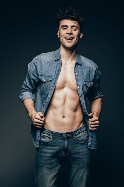 happy muscular man posing in denim clothes isolated on dark grey - Photo, Image