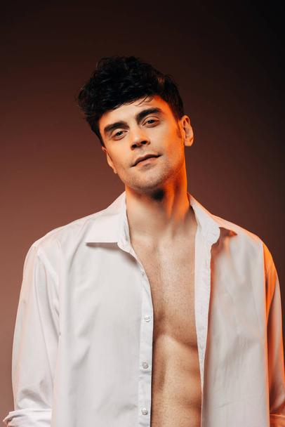 fashionable sexy man posing in white shirt, isolated on brown - Photo, Image