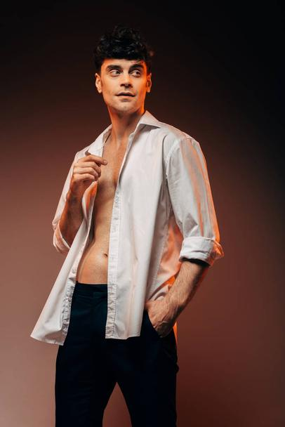 handsome sexy man posing in white shirt, isolated on brown - Photo, Image