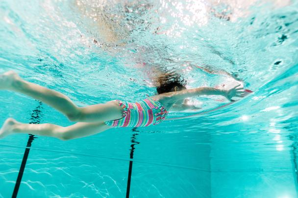 kid swimming in blue water in swimming pool  - Photo, Image