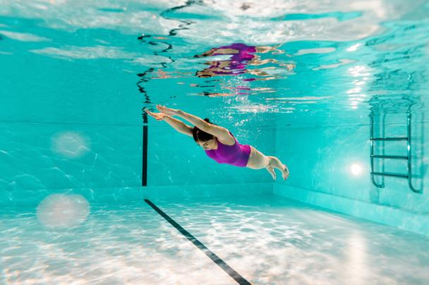 woman diving underwater in pink swimsuit in blue water of swimming pool - Photo, Image