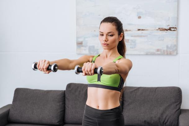 selective focus of beautiful sportswoman working out with dumbbells at home - Photo, Image