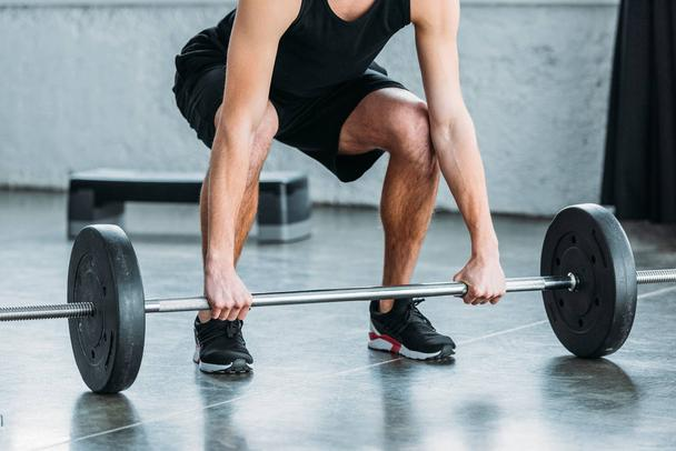 cropped shot of muscular young man in sportswear lifting barbell in gym - Photo, Image