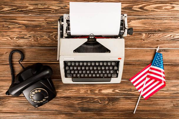 top view of typewriter, rotary dial telephone and american flag on wooden table - Photo, Image